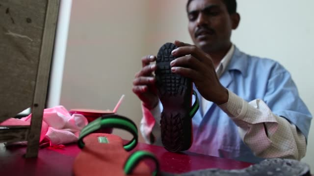 An employee measures the length of a strap at the Greensole sample workshop in Mumbai India on Monday Aug 8 An employee applies a label to a shoe...