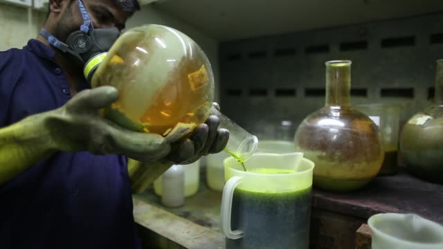 an employee mixes a flask of aqua regia or nitrohydrochloric acid for a photograph inside the gold refinery unit at kama schachter jewelry pvt ltd in... - hydrochloric acid stock videos and b-roll footage