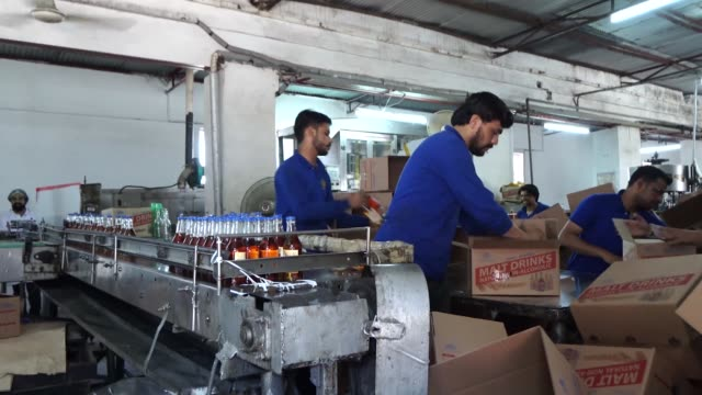 an employee monitors a bottlelabelling machine at the murree brewery co factory in rawalpindi punjab pakistan on saturday may 13 2017 cu a labelling... - punjab pakistan stock videos and b-roll footage