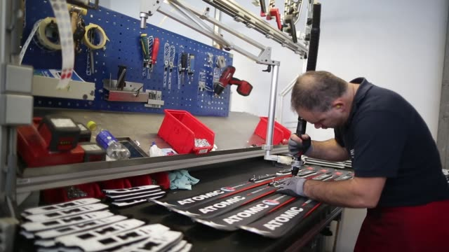 An employee mounts bindings onto Redster X5 Slope skis on the production line at the Atomic Austria GmbH a unit of Amer Sports Oyj pro center...
