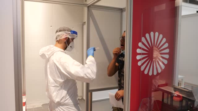 an employee of a private covid-19 test centre dressed in full ppe takes a throat swab sample from a passenger in terminal 1 of the new ber berlin... - wissenschaftliches experiment stock-videos und b-roll-filmmaterial
