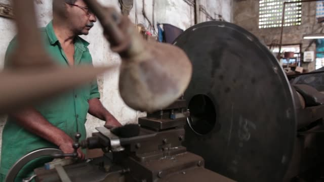 an employee operates a metal lathe inside an ishwar engineering co. factory in mumbai, maharashtra, india, on saturday, feb. 7, 2015 - indian subcontinent ethnicity stock videos & royalty-free footage