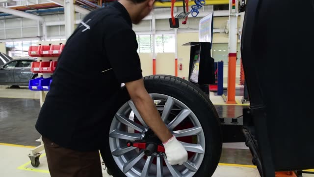 an employee operates a tyre machine at the assembly line of a pt gaya motor factory in jakarta indonesia on wednesday nov 30 an employee assembles a... - southeast asian ethnicity stock videos & royalty-free footage