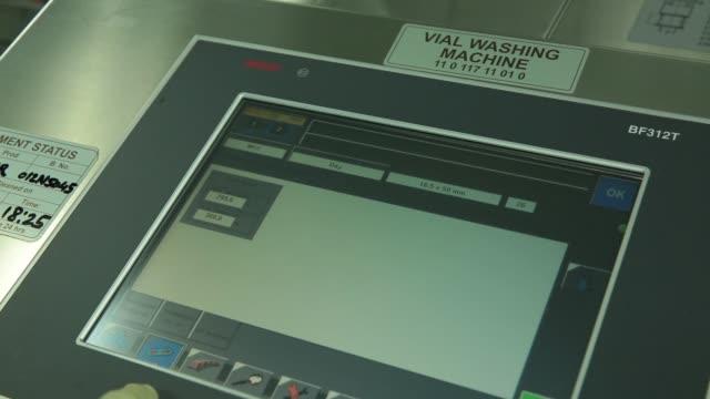 stockvideo's en b-roll-footage met an employee operates a vial washing machine unit, an employee loads empty vials into a vial washing machine, empty vials move along a conveyor... - medicijnflesje