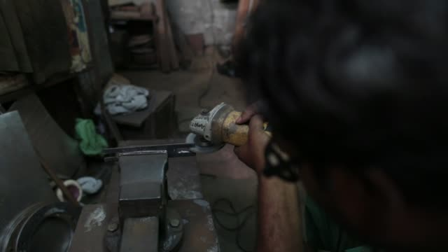 an employee operates an angle grinder inside an ishwar engineering co factory in mumbai maharashtra india on saturday feb 7 2015 - 研ぐ点の映像素材/bロール