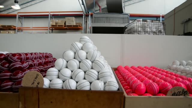 an employee packs white cricket balls in a box by hand at the kookaburra sports pty ltd plant in moorabin australia on tuesday nov 26 lacquered red... - cricket ball stock videos & royalty-free footage