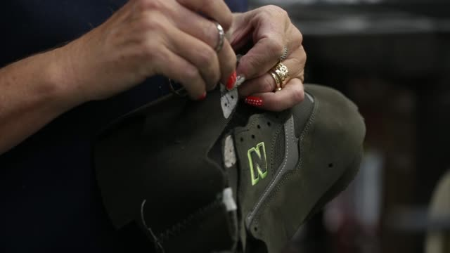 An employee places New Balance Athletic Shoe Inc trainer sections into position during the manufacturing process at the company's factory in Flimby...