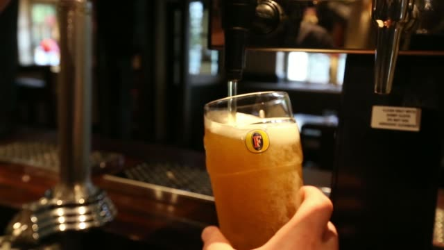 An employee pours a glass of draft Fosters from behind the bar inside The Yew Tree pub operated by Chef and Brewer a unit of Spirit Pub Co in Great...
