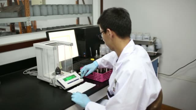 an employee prepares to weigh flasks containing a solution of liquid and coal on a scale at a bureau veritas sa inspection and testing laboratory in... - liquid solution stock videos and b-roll footage