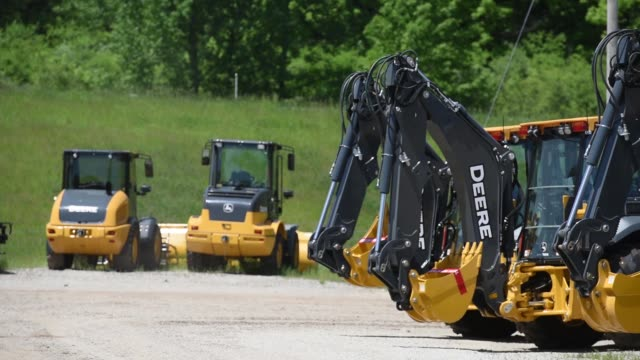 An employee preps a John Deere Co excavator for sale at Martin Equipment in Rock Island Illinois US on Friday May 22 2015