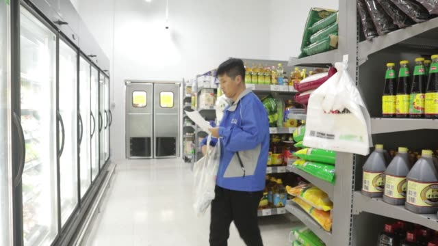 stockvideo's en b-roll-footage met an employee pushes a shopping basket while fulfilling an electronic order in a walmart stores inc miniwarehouse for the company's onehour delivery... - wal mart