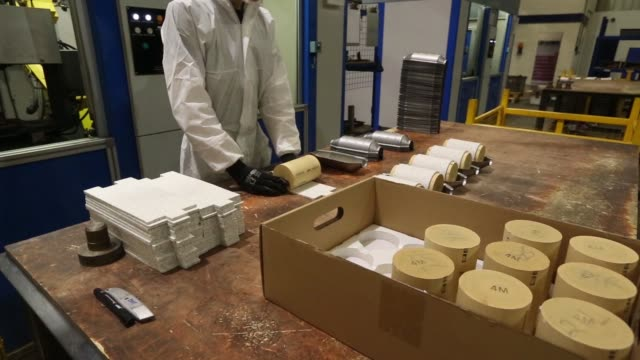an employee puts together an automobile catalytic converter emission control device using a 'brick' or monolith, that contains platinum, at bm... - platinum stock-videos und b-roll-filmmaterial