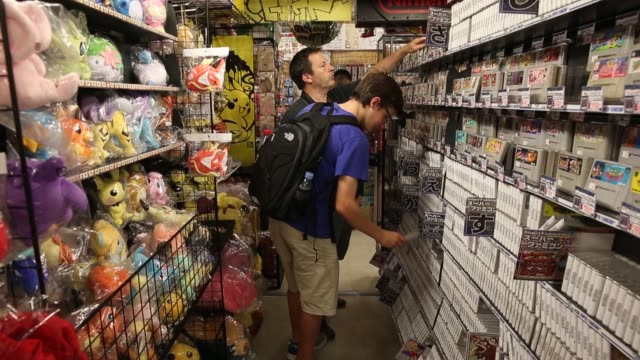 An employee right arranges video games on shelves at the Super Potato video game store in the Akihabara district of Tokyo Japan on Tuesday Aug 8...