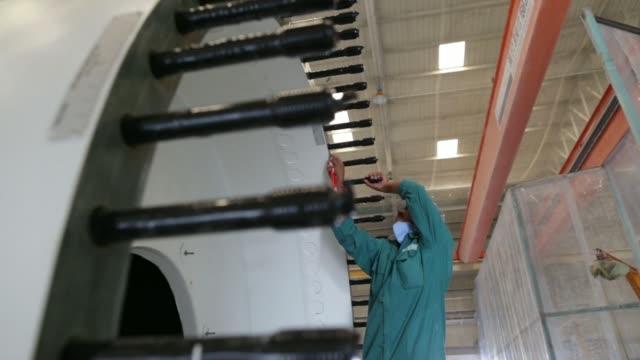 An employee rubs down a wind turbine blade An employee inspects a finished wind turbine blade An employee walks between two finished wind turbine...