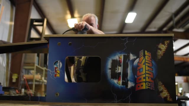 an employee sands down the sides of a vertigo style virtual pinball machine cabinet preparing it so decals can be put on the sides of it at vpcabs in... - pinball machine stock videos & royalty-free footage