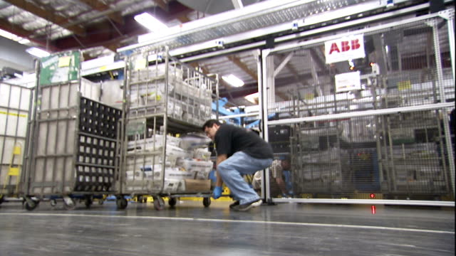 vídeos de stock, filmes e b-roll de an employee secures a cart and moves it out of a processing area. - united states postal service