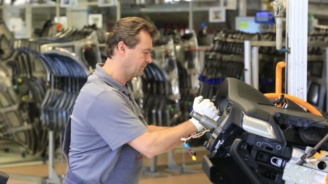 an employee secures electrical cables into a porsche 911 luxury automobile on the assembly line at porsche ags factory operated by volkswagen ag in... - nordeuropäischer abstammung stock-videos und b-roll-filmmaterial