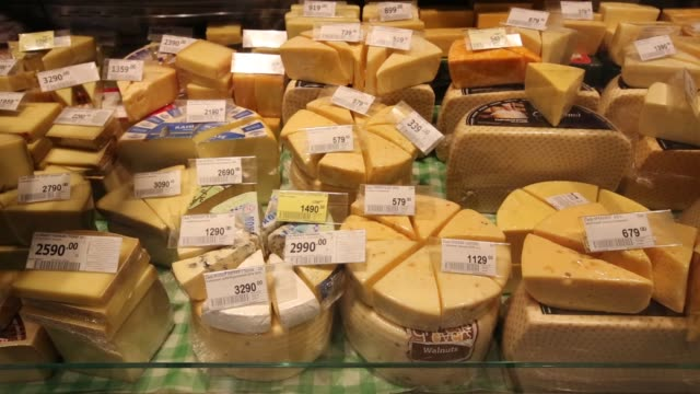 an employee selects a block of cheese for a customer inside a perekrestok supermarket operated by x5 retail group in moscow russia on tuesday feb 4... - financial accessory stock videos & royalty-free footage