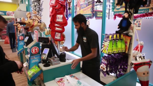 An employee serves a customer paying with cash at the checkout counter inside a Poundland discount store operated by Poundland Group Plc in the...