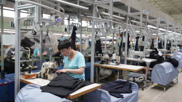 An employee sews fabric pieces at a factory operated by the Shandong Ruyi Technology Group in Jining China on Monday May 30 An employee uses a sewing...