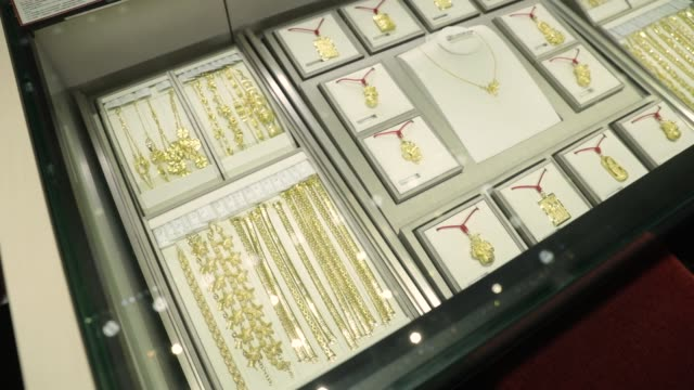 an employee shows jewelry to customers at a chow tai fook jewellery group ltd. store in shanghai, china, on thursday, feb. 1 gold necklaces sit in a... - display cabinet stock videos & royalty-free footage