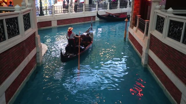 An employee steers a gondola with guests inside The Venetian Macao resort and casino operated by Sands China Ltd a unit of Las Vegas Sands Corp An...