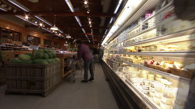 an employee stocks the shelves in a supermarket deli as customers shop. - scaffale video stock e b–roll