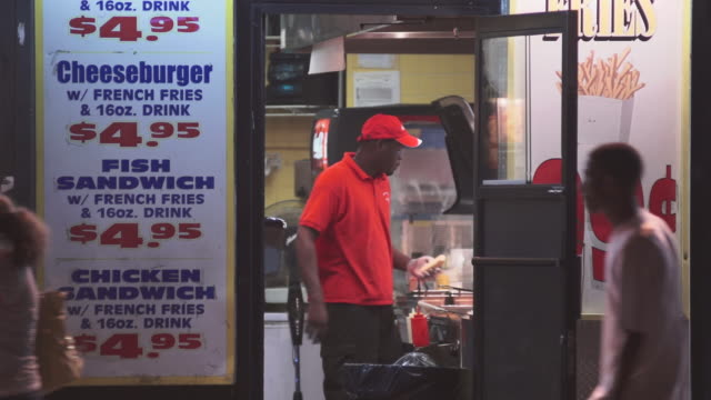 an employee stuffs a hot dog bun at a fast food place in the city. - unhealthy eating stock videos & royalty-free footage
