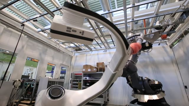 vídeos y material grabado en eventos de stock de an employee uses a kuka ag robotic arm while working on the xray detector of a siemens artis pheno angiography system on the assembly line at the... - arteriograma