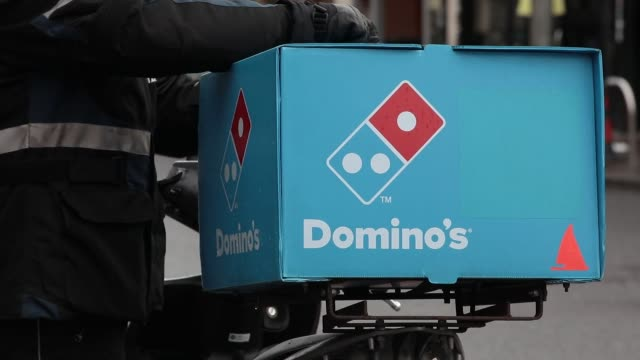 an employee uses a pizza cutter to slice a freshly cooked pizza ahead of delivery inside a domino's pizza group plc store in hanwell, london, u.k.,... - fast food stock videos & royalty-free footage