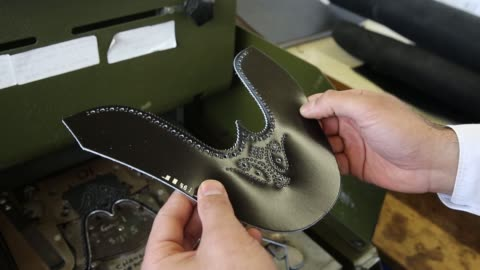 an employee uses a press to pattern leather from a template on the crockett and jones production line at the crockett & jones ltd shoe factory in... - northampton stock-videos und b-roll-filmmaterial