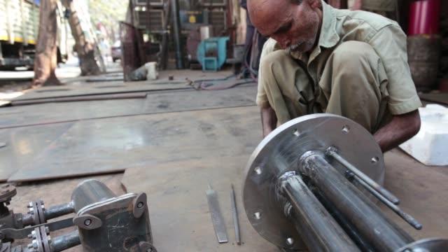 an employee uses a saw to cut a small metal pipe inside an ishwar engineering co factory in mumbai maharashtra india on saturday feb 7 2015 - 小さい点の映像素材/bロール