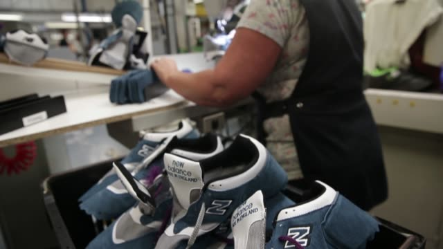 An employee uses a sewing machine as she works on an upper for a New Balance Athletic Shoe Inc trainer during the manufacturing process at the...