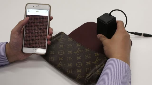 an employee uses an entrupy inc device and smartphone app to verify the authenticity of a lvmh moet hennessy louis vuitton se handbag during a... - verification stock videos & royalty-free footage
