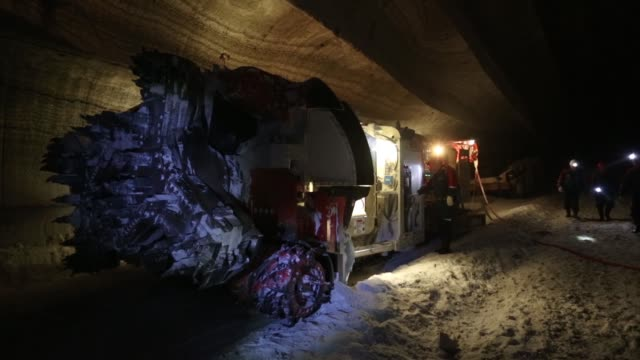 an employee uses the light from a head torch to illuminate the machine cut walls of a potash mine operated by oao uralkali in berezniki russia on... - bergwerk stock-videos und b-roll-filmmaterial