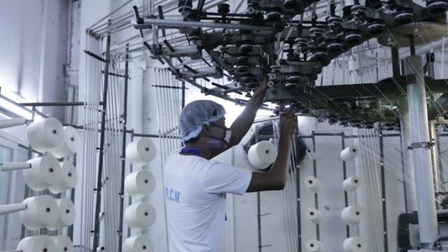 An employee wearing a face mask inspects a circular knitting machine at a Rajlakshmi Cotton Mills Ltd garment factory in Kolkata West Bengal India on...