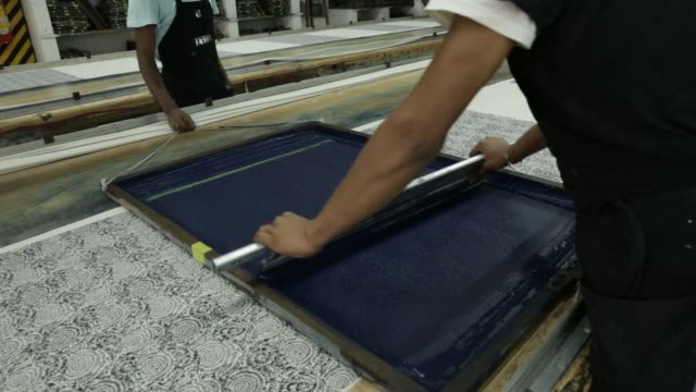 an employee wearing a face mask screen prints a design at a rajlakshmi cotton mills ltd. garment factory in kolkata, west bengal, india, on monday,... - textile industry stock videos & royalty-free footage