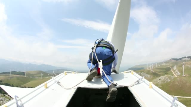 An employee wearing a safety harness and hard hat climbs through a hatch to the top of a wind turbine unit manufactured by Gamesa Corp Tecnologica SA...