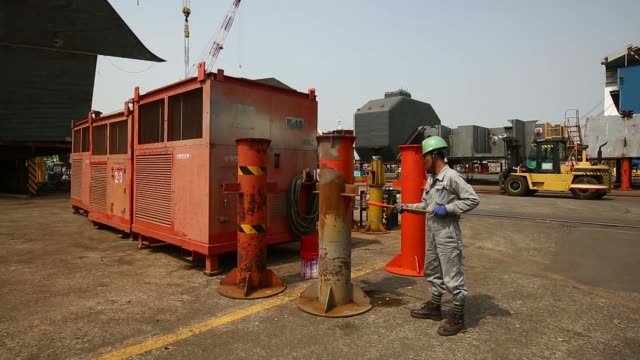 an employee welds a component of a ship under construction at the hyundai mipo dockyard co shipyard an employee paints a jig at the hyundai mipo... - 造船所の労働者点の映像素材/bロール