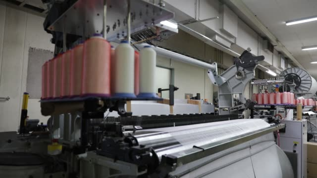 an employee works at hironen textile industry co factory in sakai fukui prefecture japan on tuesday oct 10 close up spools of thread feed into a... - loom stock videos & royalty-free footage