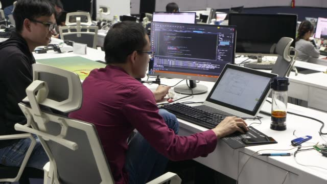 An employee works on a computer on a desk in a testing facility at the EHang Inc headquarters in Guangzhou China on Thursday Nov 2 Employees work in...