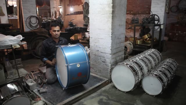An employee works on a drum in the drum department of the Nadir Ali Co factory operated by Nadir Ali Wind Instruments Pvt in Meerut Uttar Pradesh...