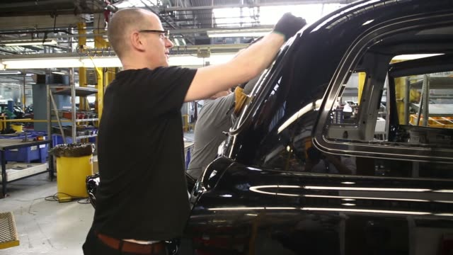an employee works on a window component of a black tx4 euro 5 london taxi cab as it moves along the production at the london taxi company's assembly... - freshly painted stock videos & royalty-free footage