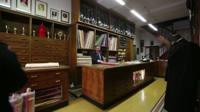 an employee works on clerical garments at the counter inside gammarelli, an ecclesiastical tailor's store in rome as womann employee leaves, red... - tape measure video stock e b–roll
