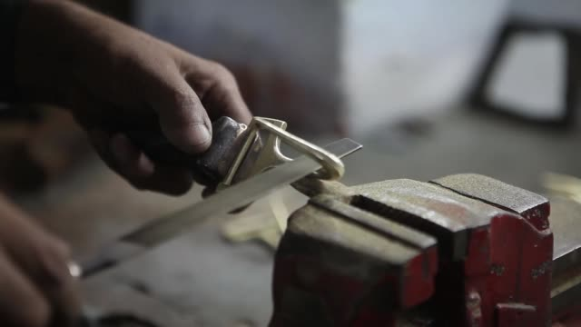an employee works on the bell component of a brass instrument on a lathe in the tool room nadir ali co factory operated by nadir ali wind instruments... - wind instrument stock videos & royalty-free footage