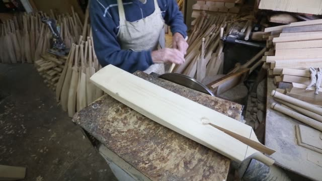 an employee works on the blade of a handmade warsop stebbing cricket bat at warsop cricket's traditional manufacturing workshop in east hanningfield... - クリケットバット点の映像素材/bロール