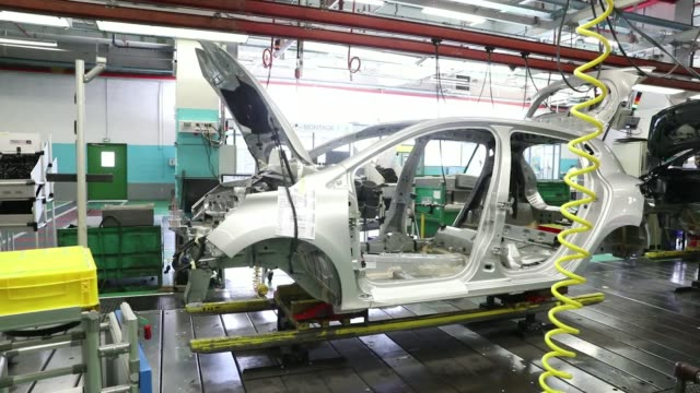 an employee works on the body shell of a freshly painted nissan micra automobile inside the renault sa factory in flins, france, on thursday, feb.... - freshly painted stock videos & royalty-free footage