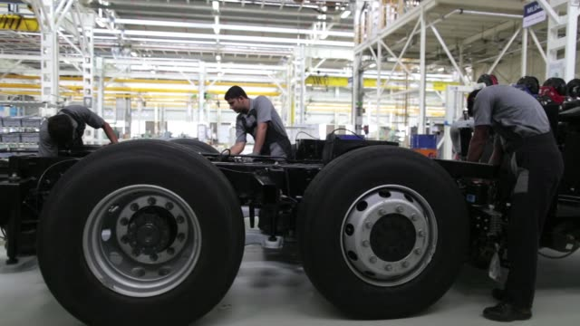vídeos de stock e filmes b-roll de ms an employee works on the chassis of a bharatbenz passenger bus production line ws employees work on the chassis of a bharatbenz passenger bus... - chassi