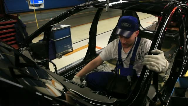 an employee works on the ford fiesta automobile production line at the ford motor co factory in cologne germany on friday march 21 the ford logo sits... - ford motor company stock videos & royalty-free footage