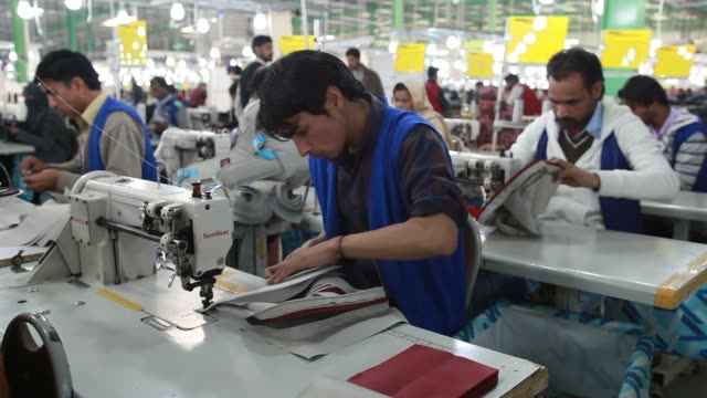 An employees machine stitches an Adidas AG Neo bag on the production line at the Forward Sports Ltd factory in Sialkot Punjab Pakistan on Tuesday Jan...